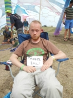 "A blond man sits in a camping chair, one eye open, one eye closed, obviously just totally hammered. A sign reading ""barrel roll"" has been placed on his lap. He looks annoyed."
